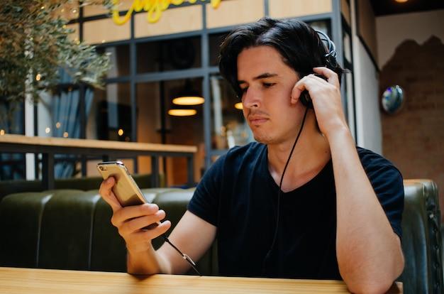 Chico escuchando música con auriculares en una cafetería.