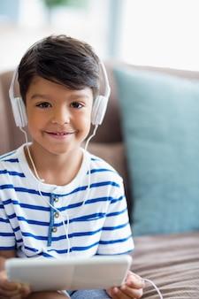 Chico escuchando música en tableta digital en la sala de estar en casa