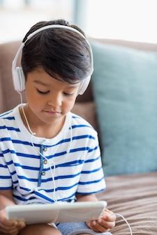Chico escuchando música en tableta digital en sala de estar
