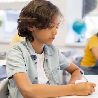 Chico en la escuela escribiendo