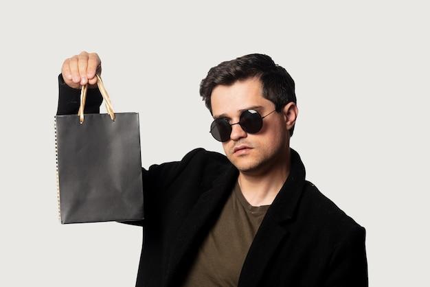 Chico de estilo en abrigo negro y gafas de sol con bolsa de compras
