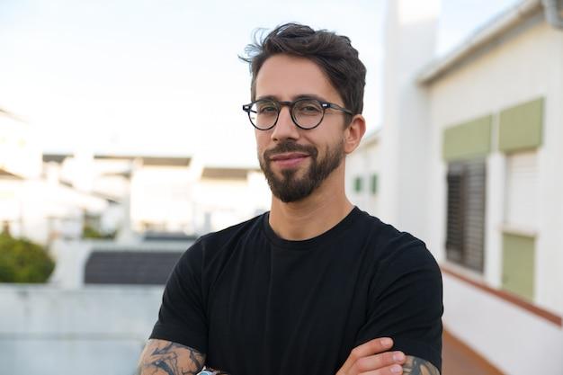 Chico con estilo alegre en gafas posando en el balcón del apartamento