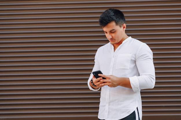 Chico con estilo joven en camisa escribiendo en el teléfono sobre fondo simple