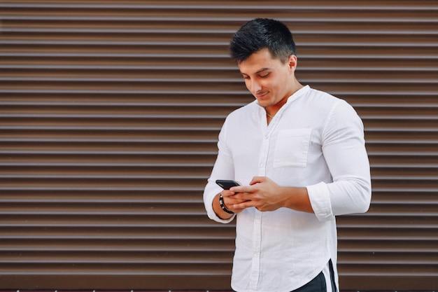 Chico con estilo joven en camisa escribiendo en el teléfono