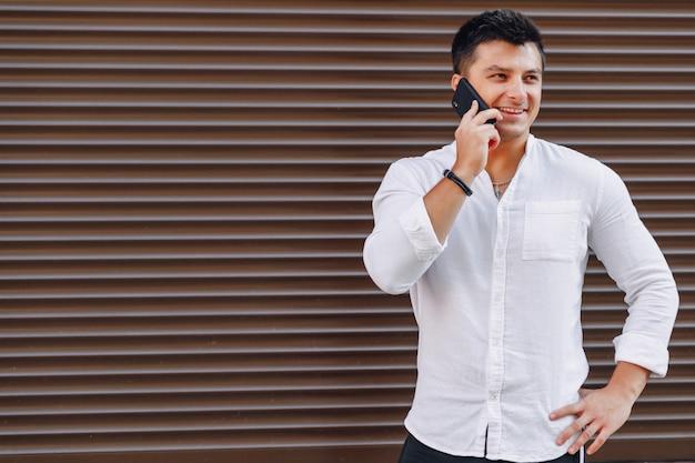 Chico con estilo joven en camisa hablando por teléfono sobre fondo simple