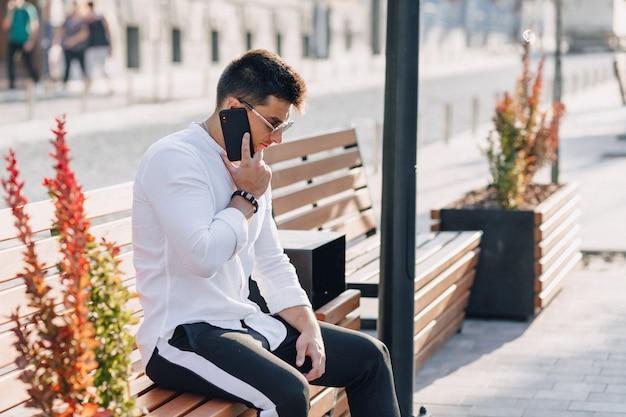 Chico con estilo joven en camisa con teléfono en el banco en un día cálido y soleado al aire libre