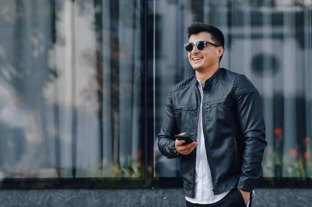 Chico con estilo joven con gafas en chaqueta de cuero negro con teléfono