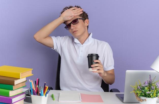 Chico estudiante en camisa polo blanca con gafas sentado en la mesa con libros sosteniendo un vaso de papel con aspecto enfermo con la mano en la frente sobre fondo azul.