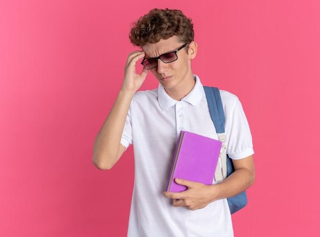 Chico estudiante en ropa casual con gafas con mochila sosteniendo portátil mirando mal tocando su cabeza que sufre de dolor de cabeza de pie sobre fondo rosa