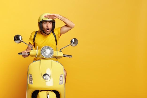 Chico estupefacto con casco conduciendo scooter amarillo