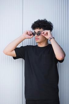Chico étnico con estilo en gafas de sol con pelo rizado