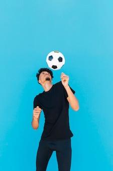 Chico étnico con pelo rizado jugando al fútbol.