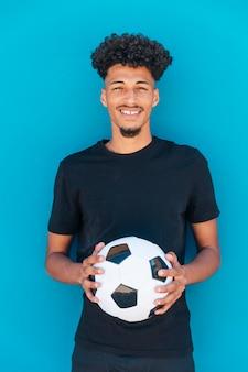 Chico étnico sonriente de pie con el fútbol