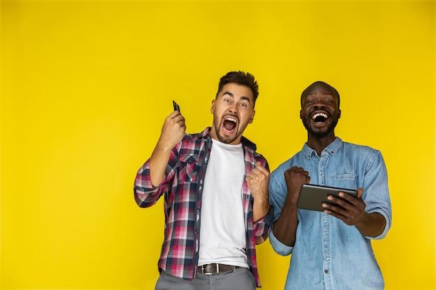El chico europeo y afroamericano está sinceramente entusiasmado con la tableta y la tarjeta de crédito en las manos