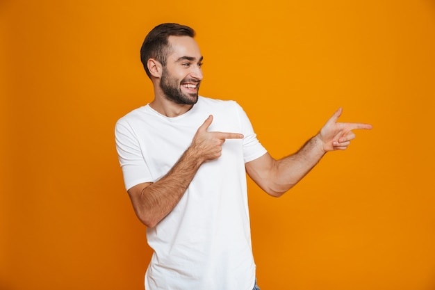 Chico europeo en camiseta apuntando con el dedo a un lado mientras está de pie, aislado en amarillo