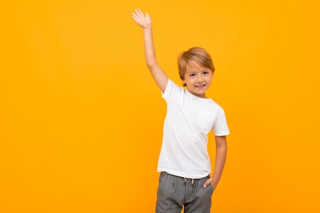 Chico europeo en una camiseta blanca con maqueta con una mano levantada sobre un amarillo con espacio de copia