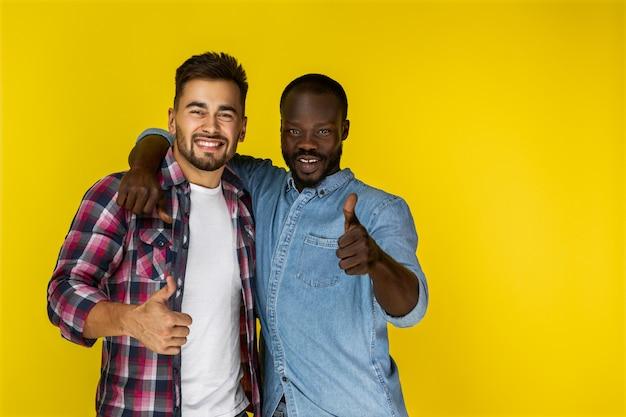 El chico europeo y el chico afroamericano se ríen y miran delante de ellos con los pulgares arriba en ropa informal