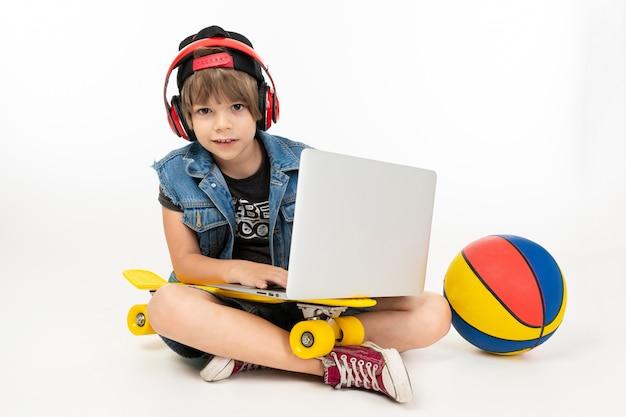 Chico europeo sentado en el suelo con portátil, patineta y baloncesto onwhite.