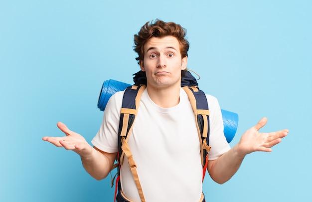 Chico excursionista que se siente desconcertado y confundido, dudando, ponderando o eligiendo diferentes opciones con expresión divertida