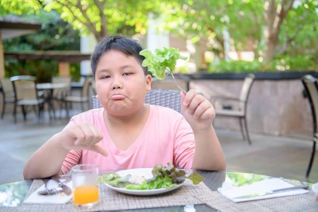 Chico con expresión de disgusto contra las verduras.