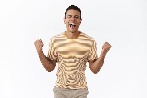 Chico feliz bombeado logra el éxito, celebrando, gritando de felicidad con los ojos cerrados y los puños apretados