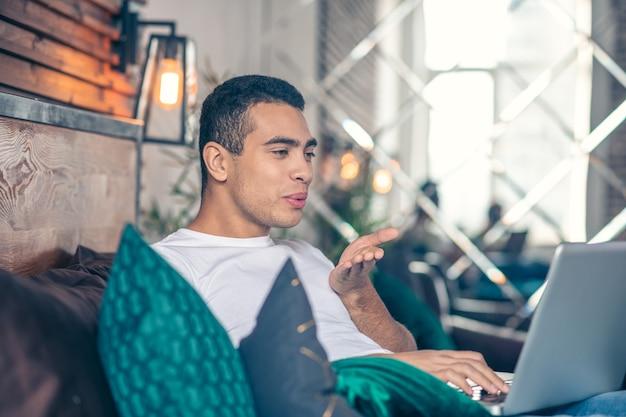 Chico feliz haciendo beso de aire en video chat mirando portátil.