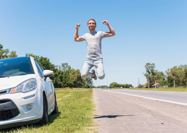 Chico feliz saltando en la carretera junto al coche