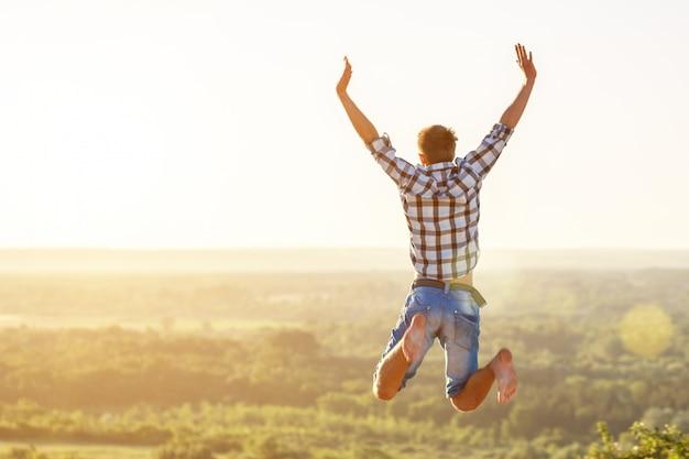 Chico feliz saltando a la cima en el fondo