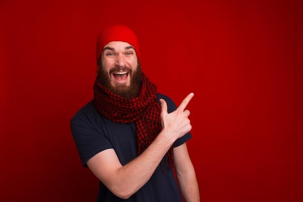 Chico feliz con sombrero rojo y bufanda, apuntando hacia otro lado mientras mira a la cámara sobre el espacio rojo
