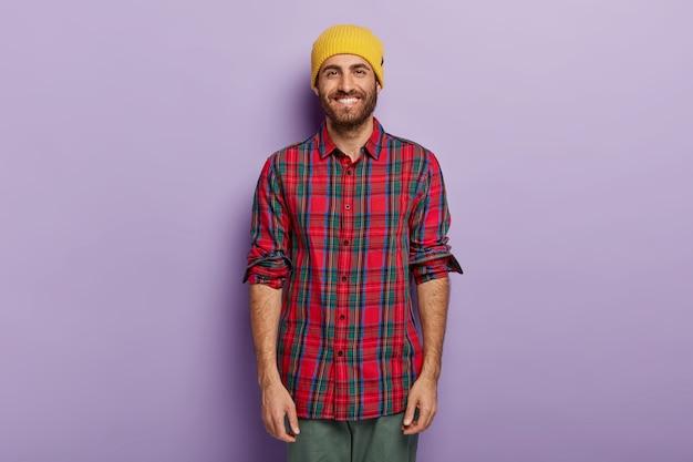 Chico feliz con sonrisa brillante, rastrojo, viste sombrero amarillo y camisa a cuadros, disfruta del tiempo libre