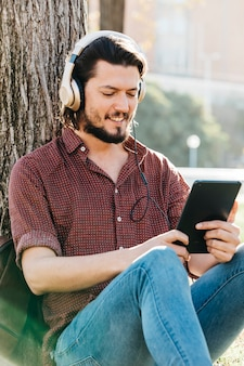 Chico feliz usando un teléfono inteligente para escuchar música con auriculares