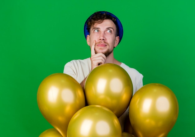 Chico de fiesta eslavo guapo joven pensativo con sombrero de fiesta de pie detrás de globos manteniendo la mano en la barbilla mirando al lado aislado sobre fondo verde