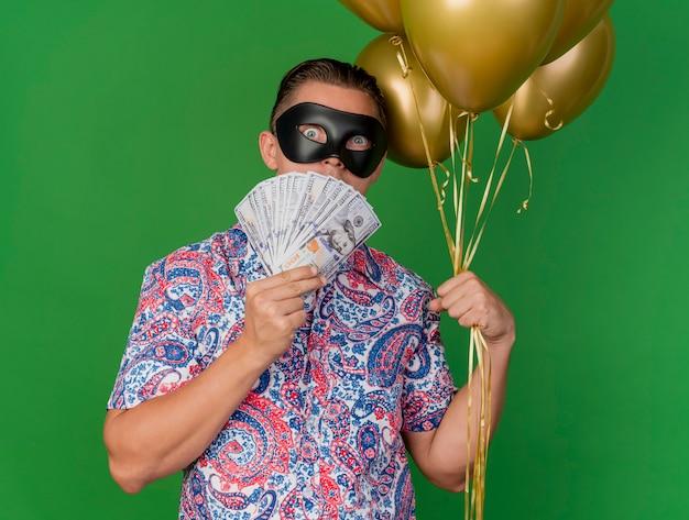 Chico de fiesta joven sorprendido con máscara de ojos de mascarada sosteniendo globos y la cara cubierta con dinero aislado sobre fondo verde