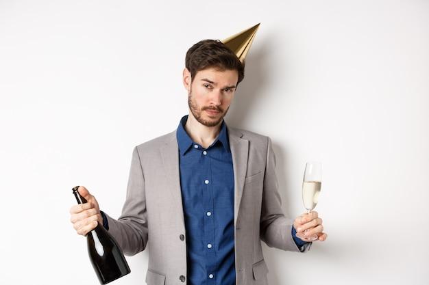 Chico fiestero de pie con sombrero de cumpleaños y celebrando, sosteniendo una botella de champán y vidrio