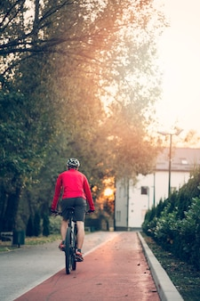 Chico fitness con bicicleta en la carretera