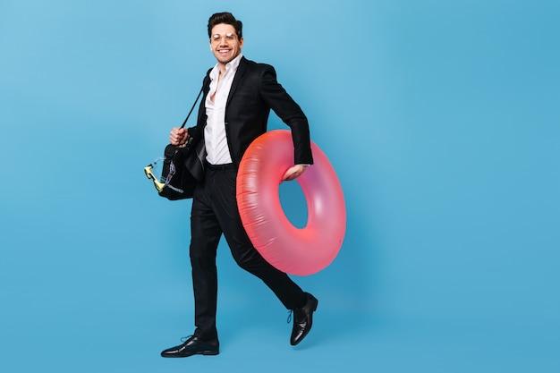 Chico de gafas tiene bolsa para portátil. hombre en traje quiere ir de vacaciones y posa con máscara de buceo y círculo inflable rosa.