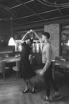 Chico girando alegre dama en restaurante