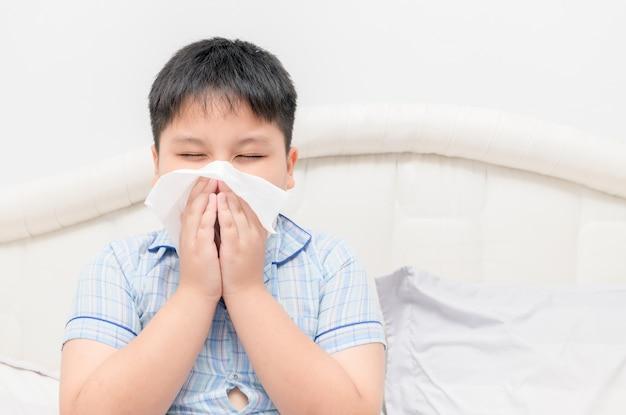 Chico gordo obeso asiático que sopla la nariz por el concepto de tejido, salud y enfermo