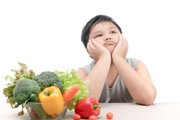 Chico gordo obeso con expresión de disgusto contra las verduras aisladas sobre fondo blanco, rechazando f