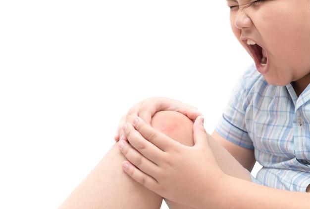 Chico gordo obeso que sufre de dolor de rodilla aislado sobre fondo blanco, problema saludable