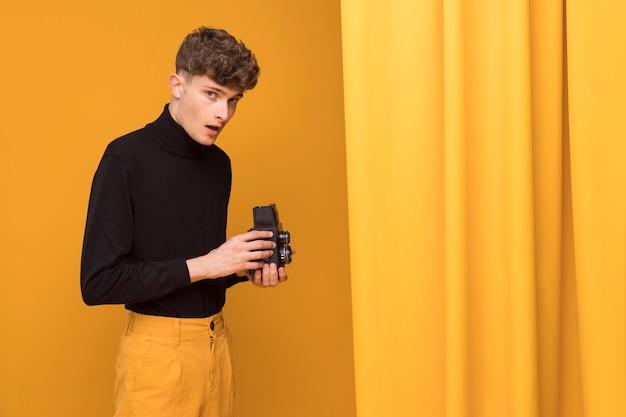 Chico grabando con un camcorder en un escenario amarillo