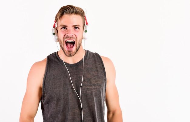 Chico gritando. la música rock. nueva tecnología en la vida moderna. hombre musculoso sexy escuchar música. hombre escucha nueva canción aislada en blanco. hombre sin afeitar en auriculares de tecnología blue tooth. concepto de vida moderna.