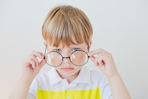 Chico guapo adolescente lleva gafas. mala visión y concepto de medicina