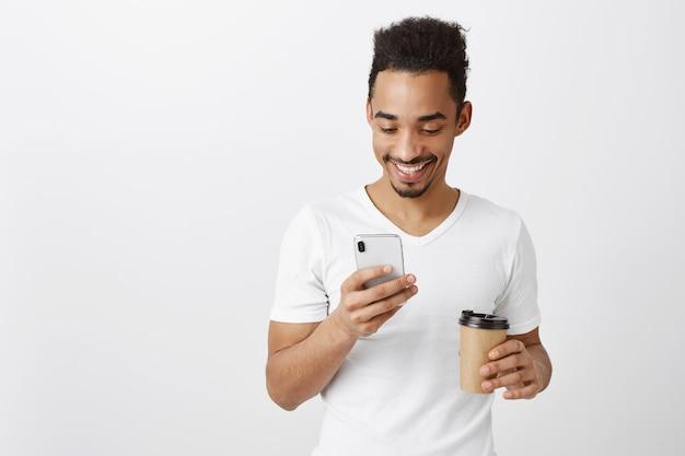 Chico guapo afroamericano en camiseta blanca charlando, enviando mensajes de texto y tomando café, mirando la pantalla del teléfono móvil