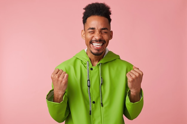 Un chico guapo afroamericano joven alegre está parado, apretó los puños, sonriendo ampliamente y absolutamente feliz: ¡ganó la lotería!