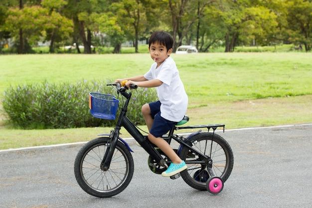 Chico guapo asiático paseo en bicicleta en el parque