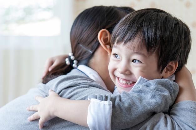 Chico guapo asiático sonriendo felizmente y abrazando con madre en casa, concepto de familia