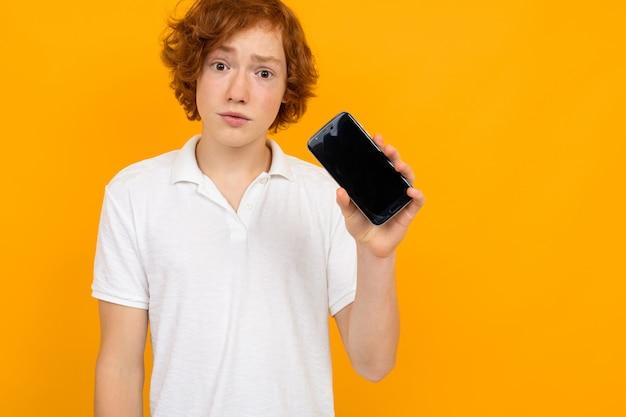 Chico guapo atractivo pelirrojo en una camiseta blanca con un teléfono con una maqueta en una pared amarilla