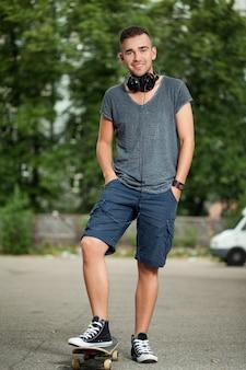 Chico guapo con auriculares y patineta