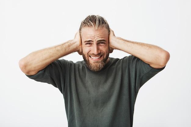 Chico guapo con barba y peinado elegante cierra las orejas con las manos